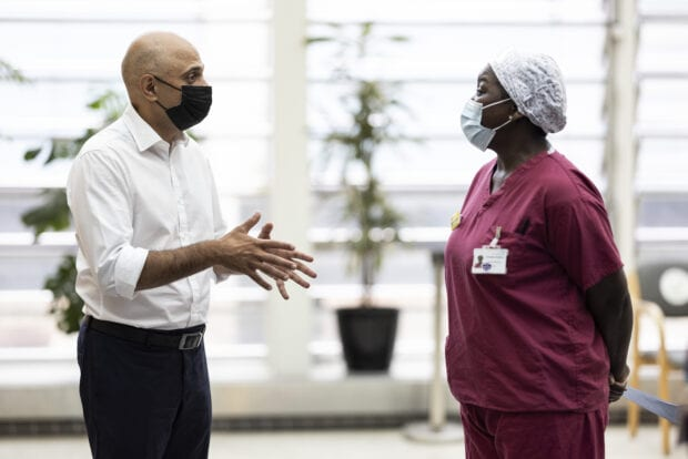Secretary of State for Health and Social Care Sajid Javid in conversation with an NHS staff member at Guys and St Thomas Hospital